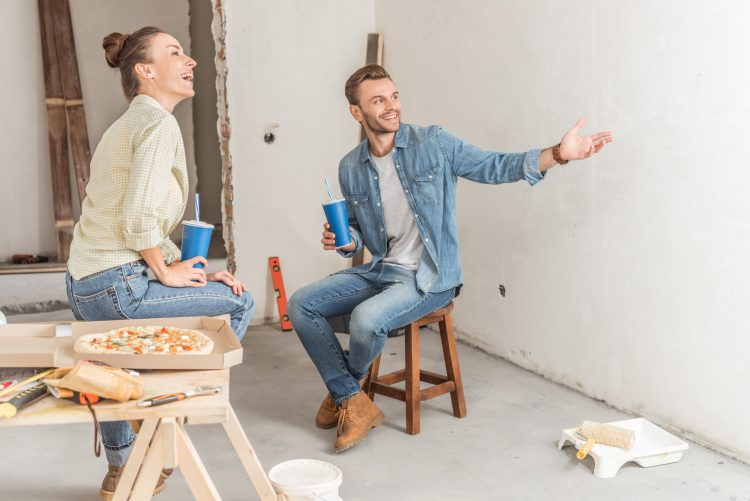 Young couple eating pizza in new house